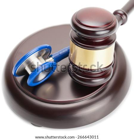 Wooden judge gavel and stethoscope near it - close up shot - stock photo
