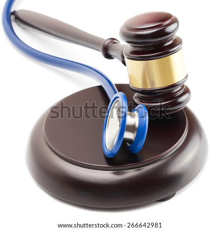 Wooden judge gavel and stethoscope next to it - close up shot - stock photo