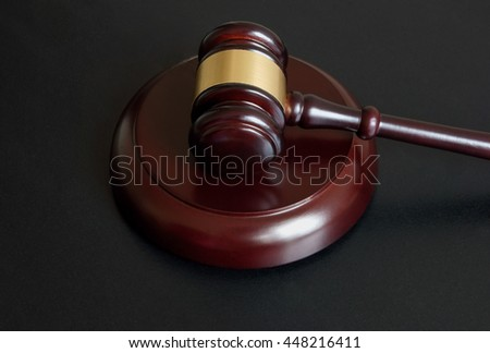 Wooden judge gavel on dark table, legal and law concept
