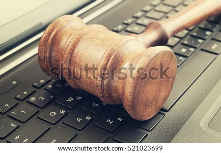 Wooden judge gavel on laptop computer, cyber law or crime concept