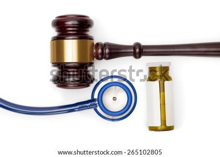 Wooden judge gavel, pills bottle and stethoscope on white backround - stock photo