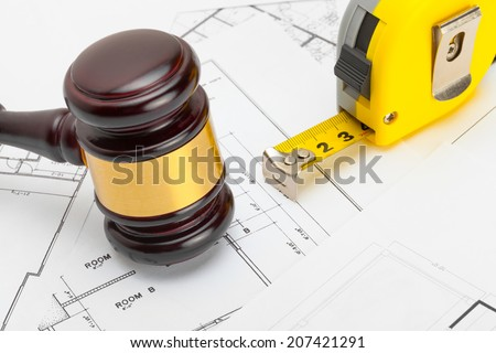 Wooden judge gavel with measure tape above construction blueprint - studio shoot - stock photo