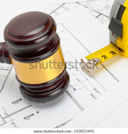 Wooden judge gavel with measure tape above over some documents - studio shoot - stock photo
