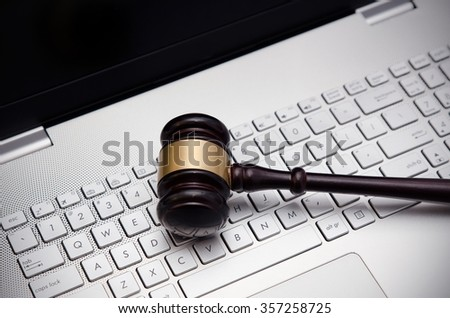 Wooden judge hammer on laptop computer white keyboard - stock photo