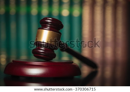 wooden judge's hammer in front of a row of law books, justice concept - stock photo