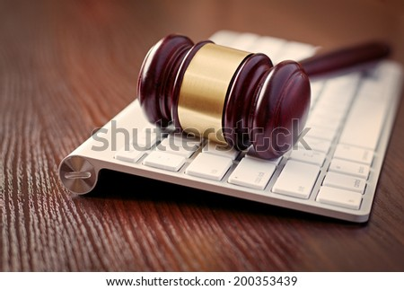 Wooden judges gavel on a computer keyboard, receding view with focus to the head with its brass decoration conceptual of online law enforcement and auctions - stock photo