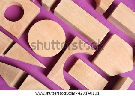 Wooden kids toys on purple background - stock photo