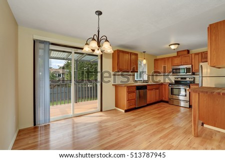 Wooden kitchen interior with hardwood floor and exit to the balcony. Northwest, USA