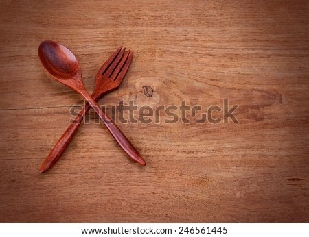 Wooden kitchen spoon on a vintage wooden board. - stock photo