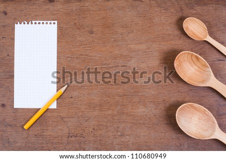 Wooden kitchen spoons on oak wood table background - stock photo