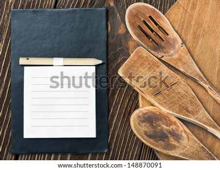 Wooden kitchen utensils and a notepad to write a recipe - stock photo
