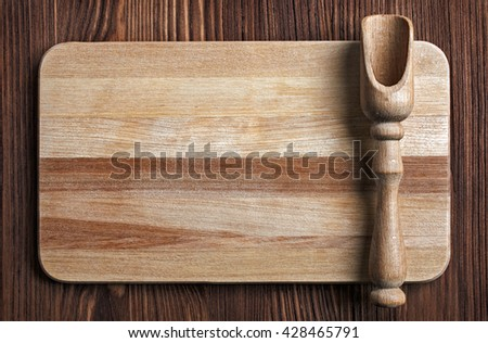 Wooden kitchen utensils on a wooden table, top view. Cutting board and shovels. - stock photo