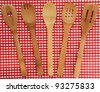 Wooden Kitchen Utensils on red and white checkered background - stock photo