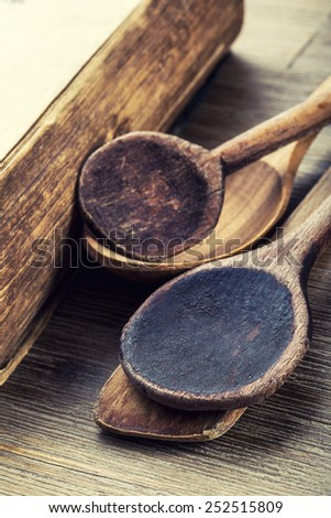 Wooden kitchen utensils on the table. Recipe book wooden spoon in a retro style on wooden table - stock photo