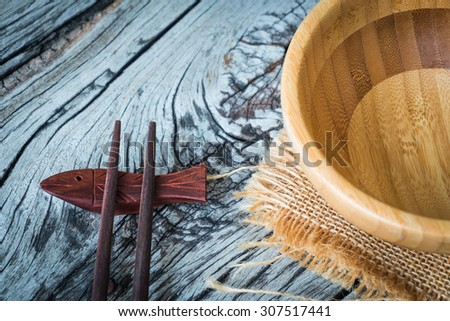 Wooden kitchenware, bowl with chopsticks on wooden background - stock photo