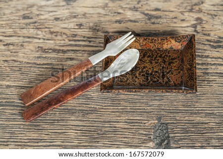 Wooden lacquer utensil with plate on wooden table (Still life) - stock photo