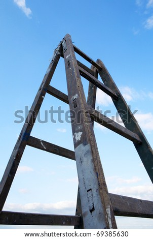 Wooden ladder from the lower perspective with the sky in the background - stock photo
