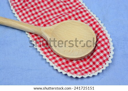 Wooden ladle on a red with white doily
