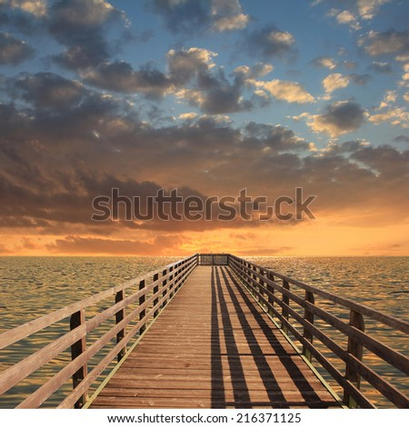 Wooden landing stage, sunset sky with clouds - stock photo