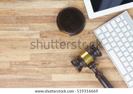 Wooden law gawel on wooden table with keyboard and tablet, judgement concept