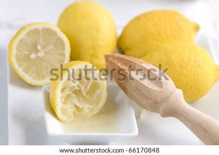 Wooden lemon squeezer with lemons and juice - stock photo