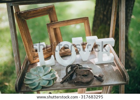 """wooden letters """"LOVE"""" are on a wooden shelf in the area for a wedding ceremony - stock photo"""