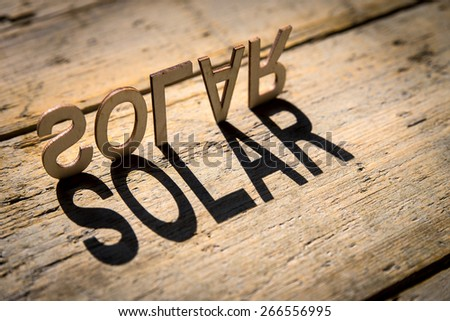 wooden letters on old aged wooden table build the shadow word solar, vintage style - stock photo