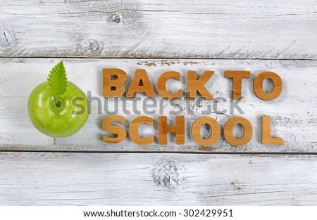 Wooden letters spelling back to school and green apple on top of rustic white boards. - stock photo