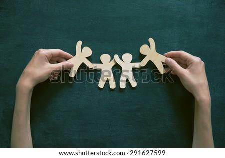 Wooden little men holding hands on blackboard background. Symbol of friendship, love or teamwork concept - stock photo