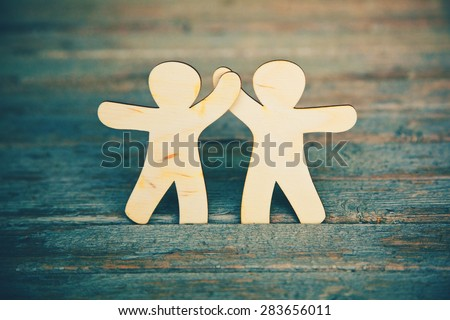 Wooden little men holding hands on wooden boards background. Symbol of friendship, love and teamwork - stock photo