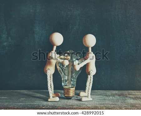 Wooden little men holding light bulb. Concept of electricity, ecology or protection - stock photo