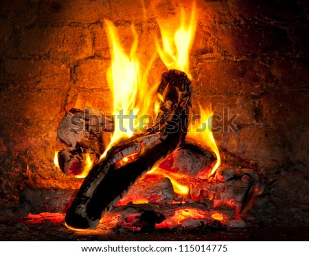Wooden log burning in the fireplace of a pizzeria Wood Oven - stock photo