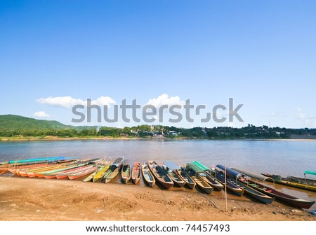 wooden long tail boats at river - stock photo