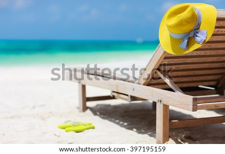Wooden lounge chairs and a yellow straw hat on a beautiful tropical beach at Maldives - stock photo