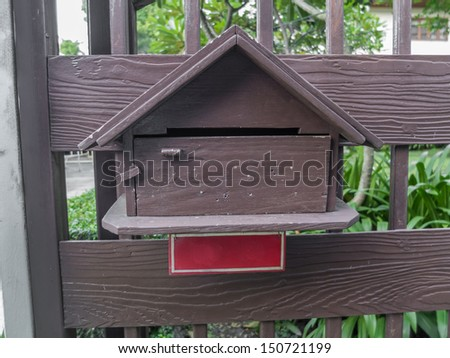 Wooden mailbox against wooden fence - stock photo