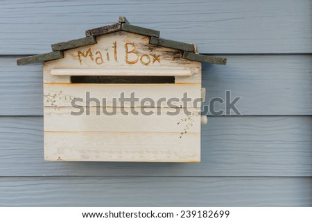 wooden mailbox on wood wall background - stock photo
