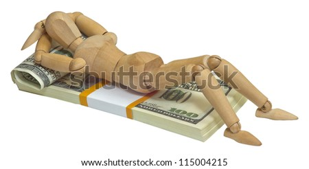 Wooden man lying on a pack of dollars are on the bed