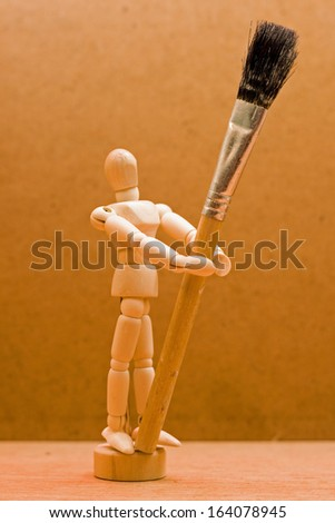 wooden manikin with large paint brush