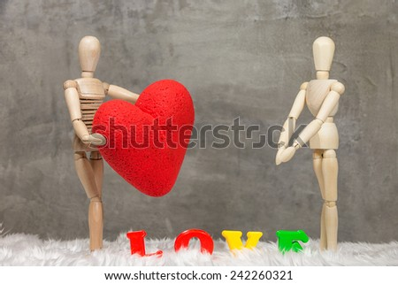 Wooden mannequin holding a heart - stock photo