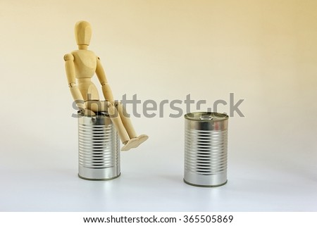 Wooden mannequin sitting on can. - stock photo