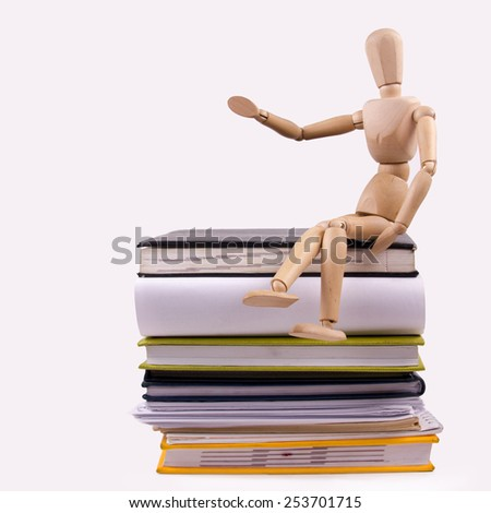 Wooden mannequin sitting on stack of books - stock photo