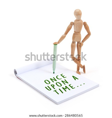 Wooden mannequin writing in a scrapbook - Once upon a time - stock photo