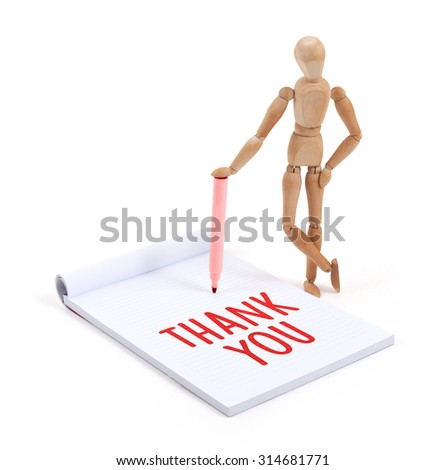 Wooden mannequin writing in a scrapbook - Thank you - stock photo