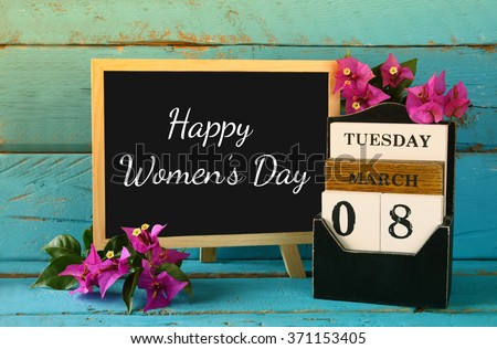 wooden March 8 calendar, next to purple flowers on old blue rustic table. selective focus. vintage filtered. Happy International Women's Day concept  - stock photo