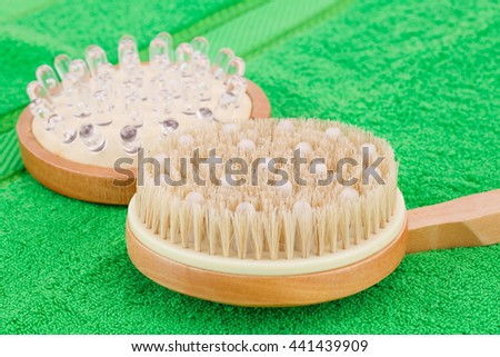 Wooden massagers on green towel, closeup picture.