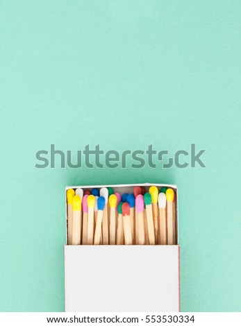 Wooden matches in pastel colors on blue