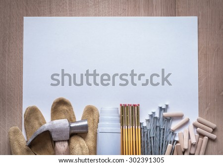 Wooden meter blueprints sheet of paper nails claw hammer fluted dowels and leather safety gloves on wood board copy space construction concept. - stock photo