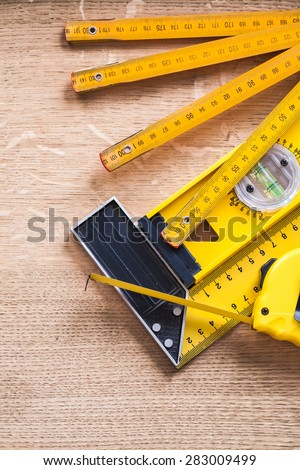 Wooden meter measuring tape construction level and square ruler on oak wood board