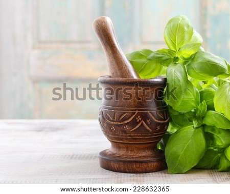 Wooden mortar and basil leaves on the table - stock photo