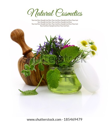 Wooden mortar and cosmetic cream jar with herbs inside - stock photo